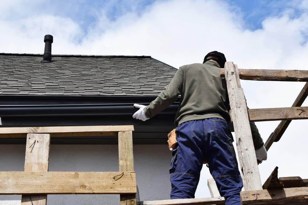 Construction,Worker,Installing,Plastic,Roof,Rain,Gutter,Gray,Shingles,Roof